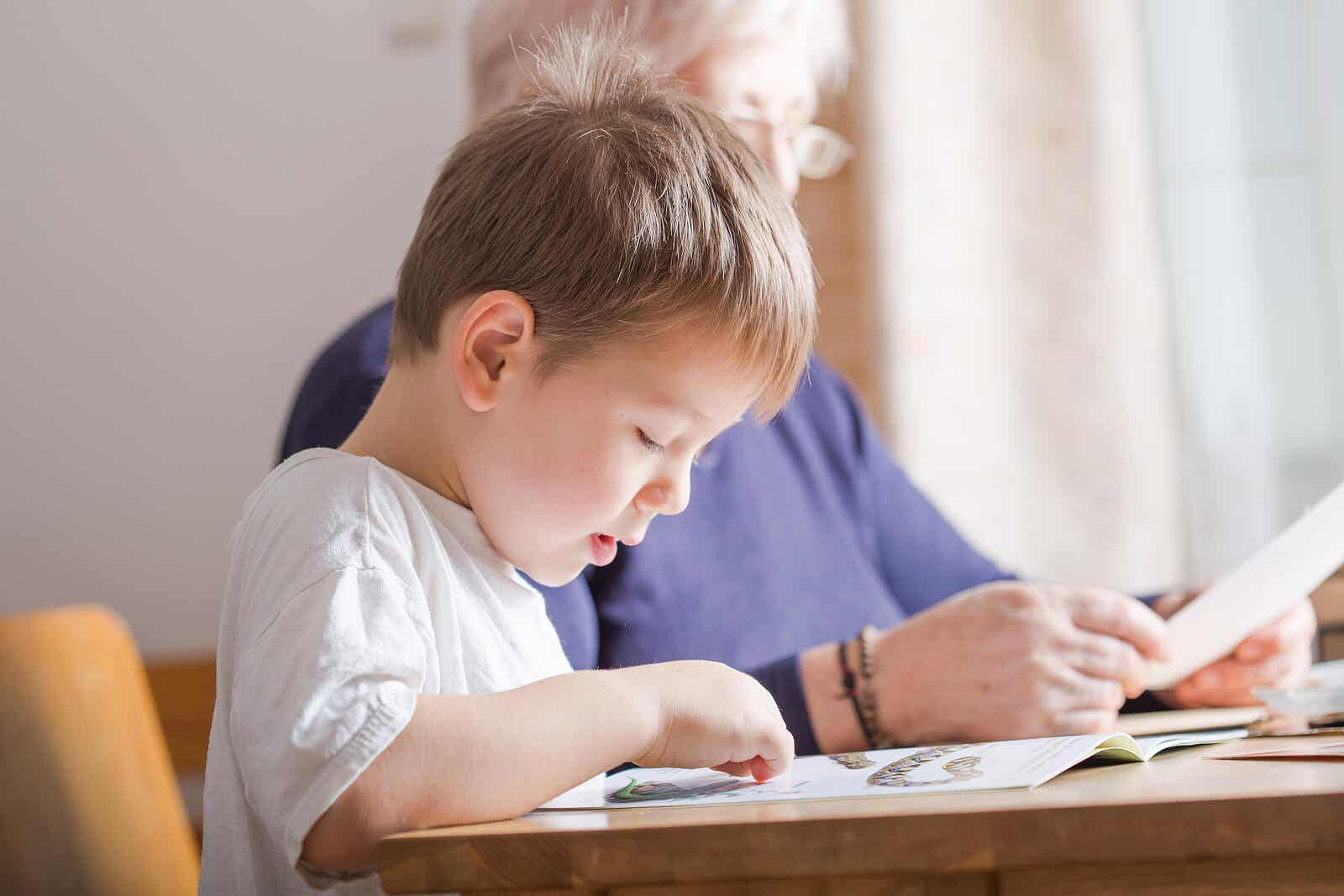 Małe dziecko czytające przy stole w pobliżu babci.