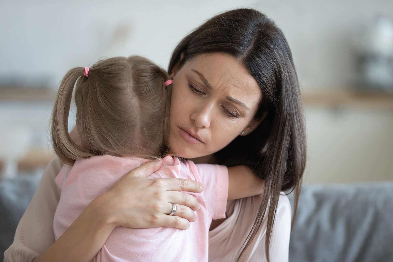 En mor som trøstet den unge datteren med en klem.
