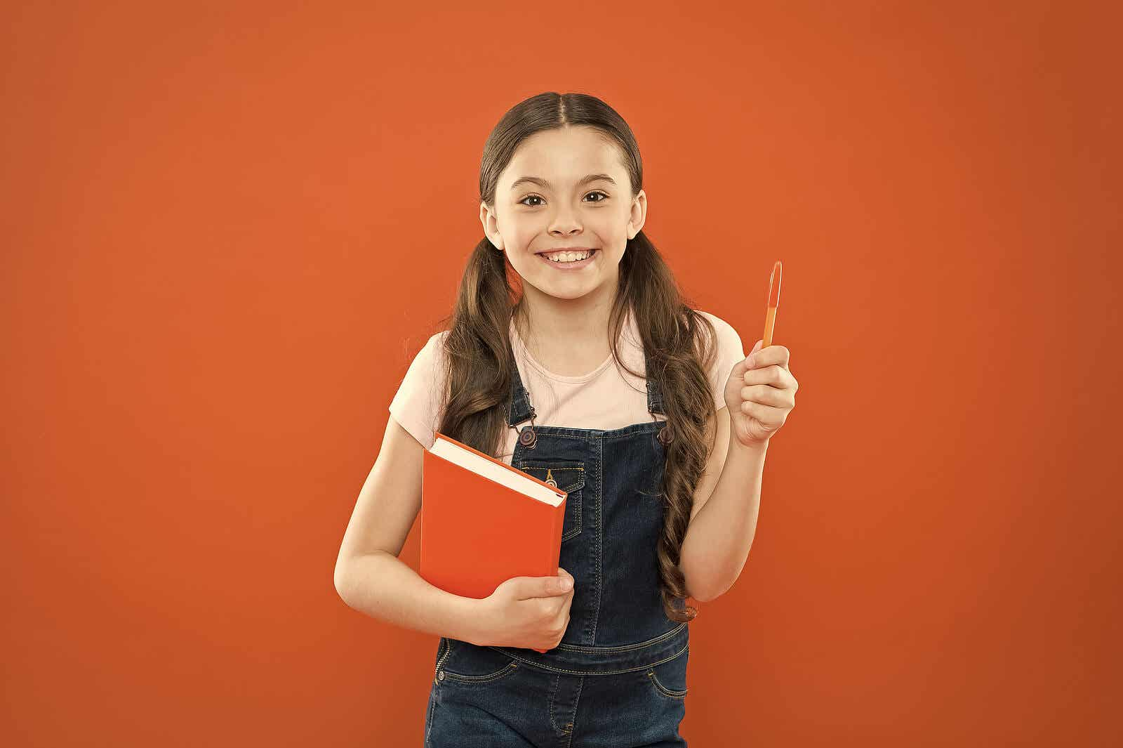 An elementary school student holding a planner and a pen.