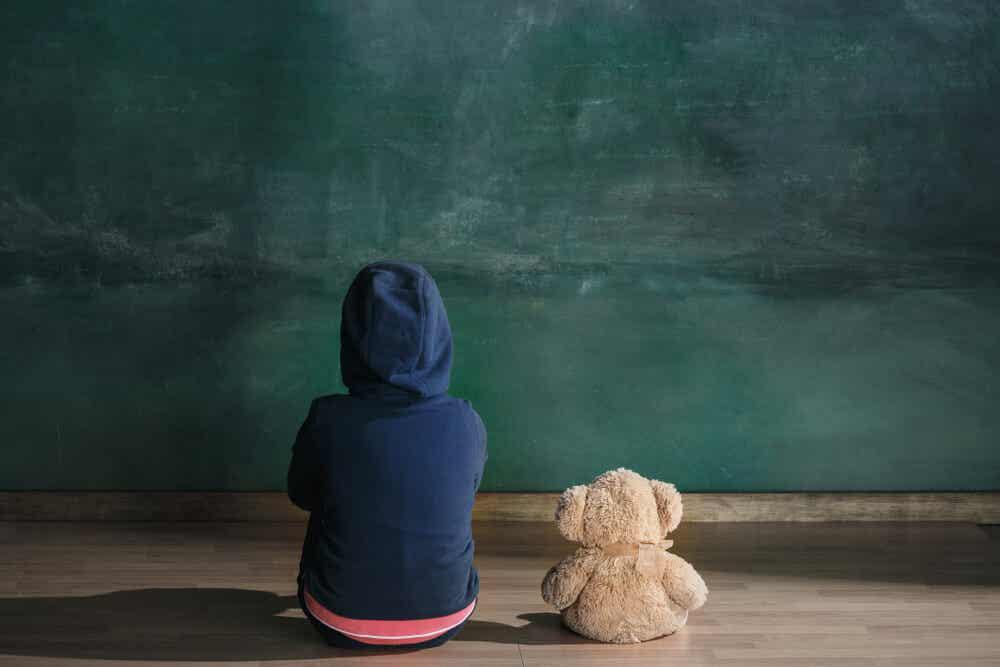 Een kind zittend op de grond naast zijn knuffelbeer, starend naar de muur.