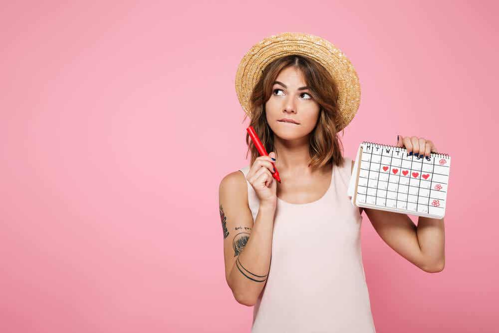 Kobieta trzymająca kalendarz z zaznaczonymi dniami jej okresu.