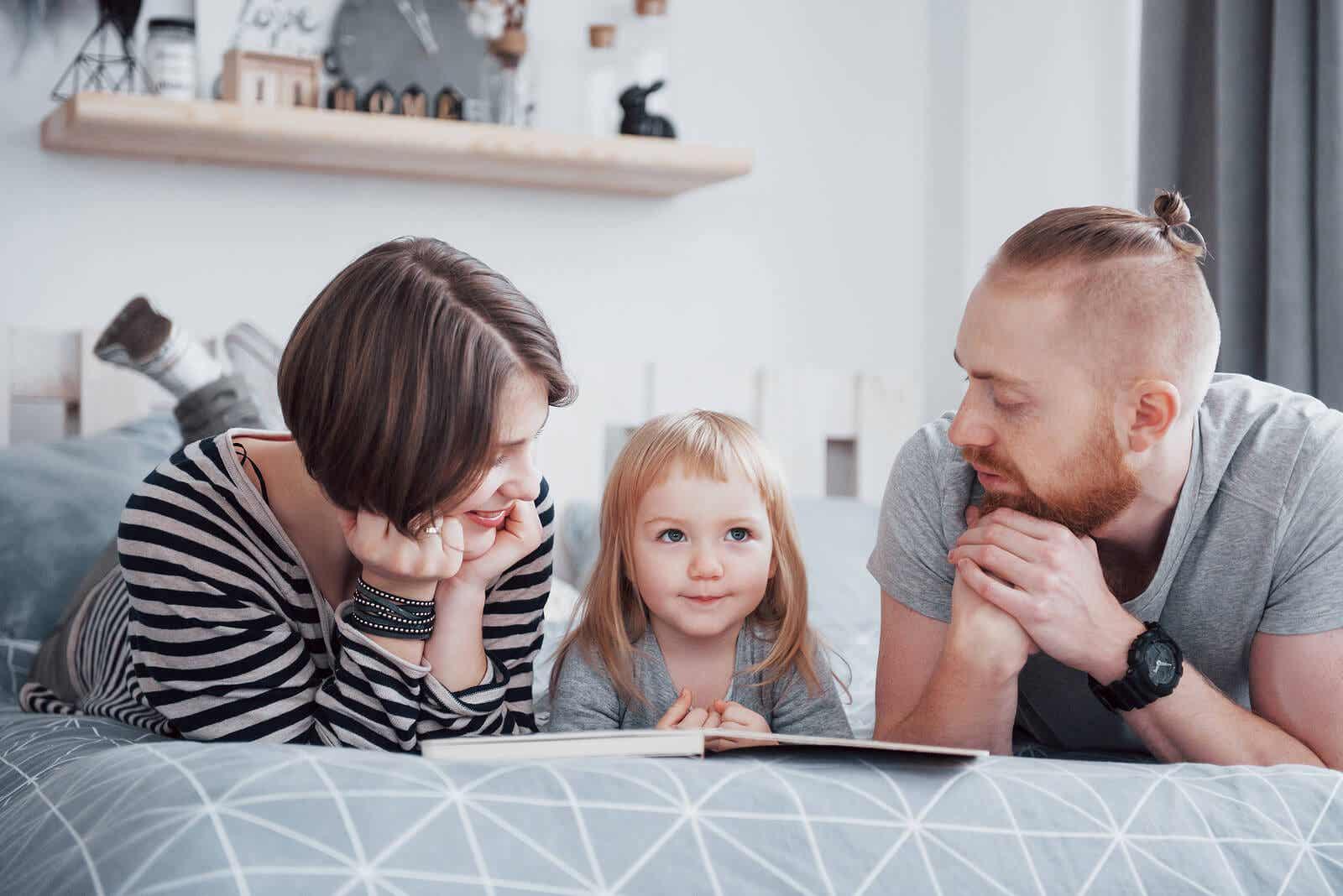 Rodzice i ich córka leżąc w łóżku, czytając książkę.