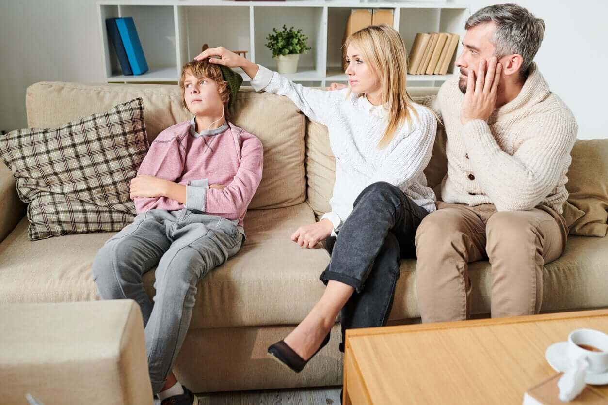 Parents with their adolescent son on the couch.