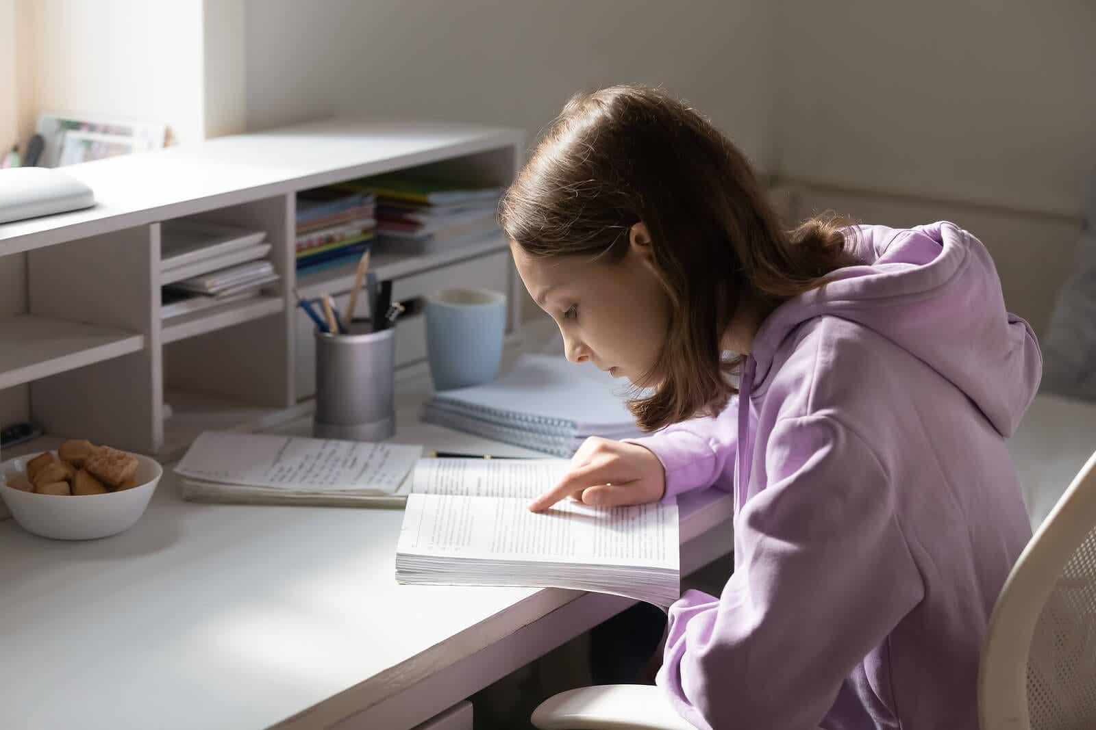 En ung flicka som studerar vid sitt skrivbord i hennes rum.
