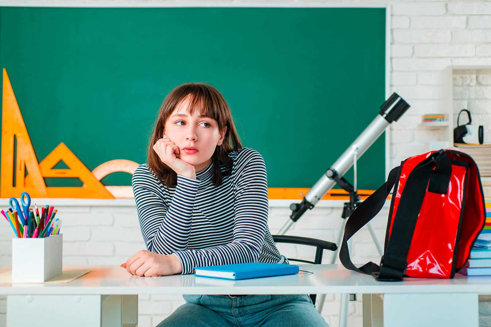 A teenager sitting in a classroom thinking.
