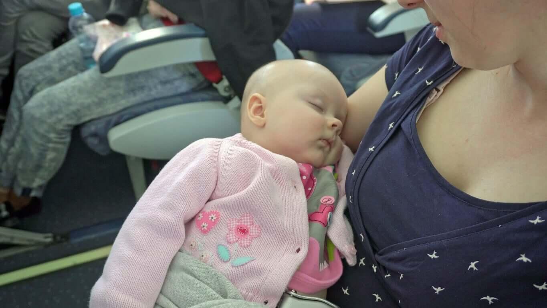 En mor holder sin sovende baby på et fly.