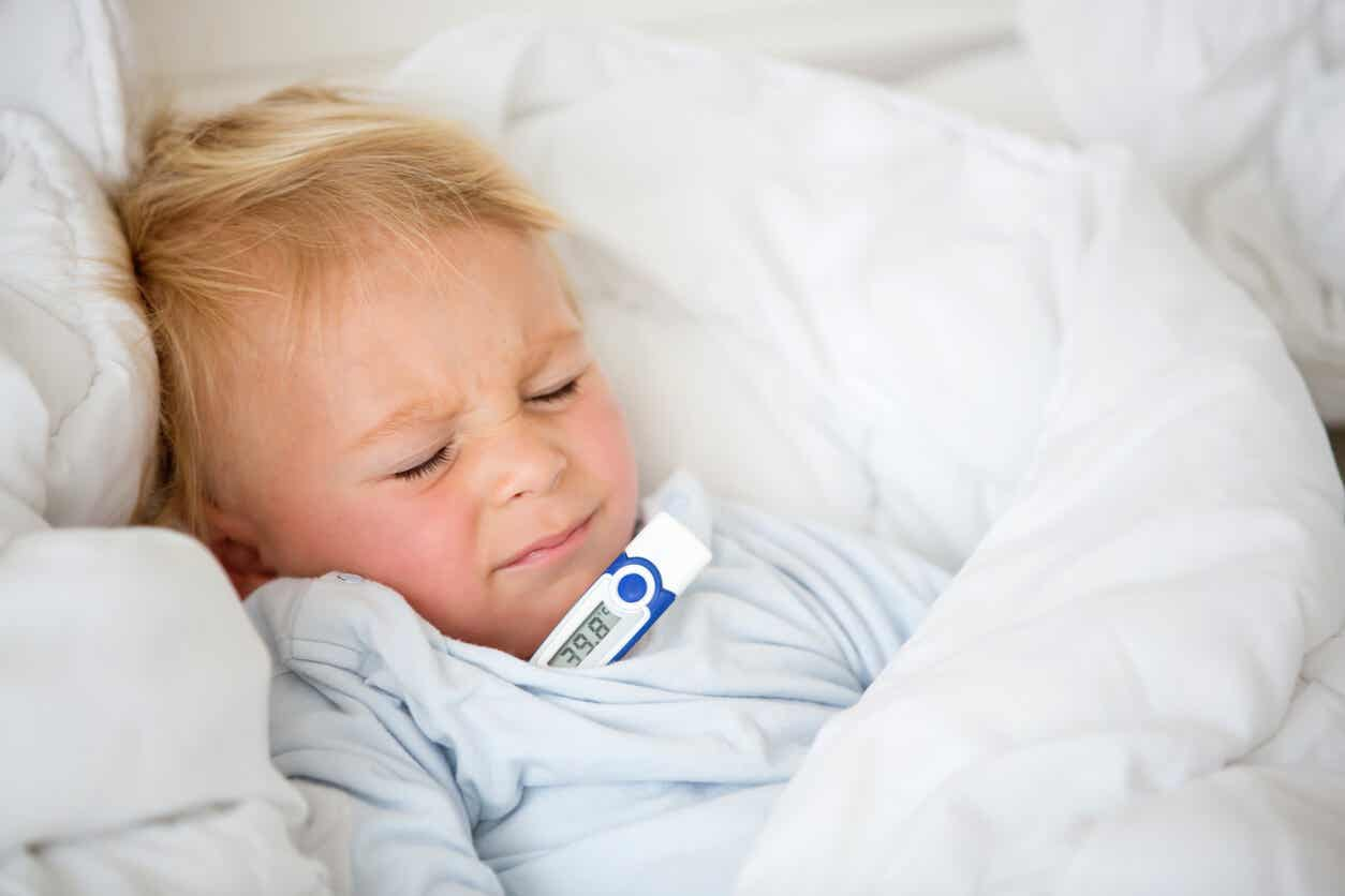 A toddler lying in bed uncomfortable, with a thermometer under his arm.