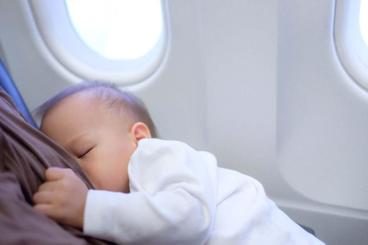 En baby sover på et fly.