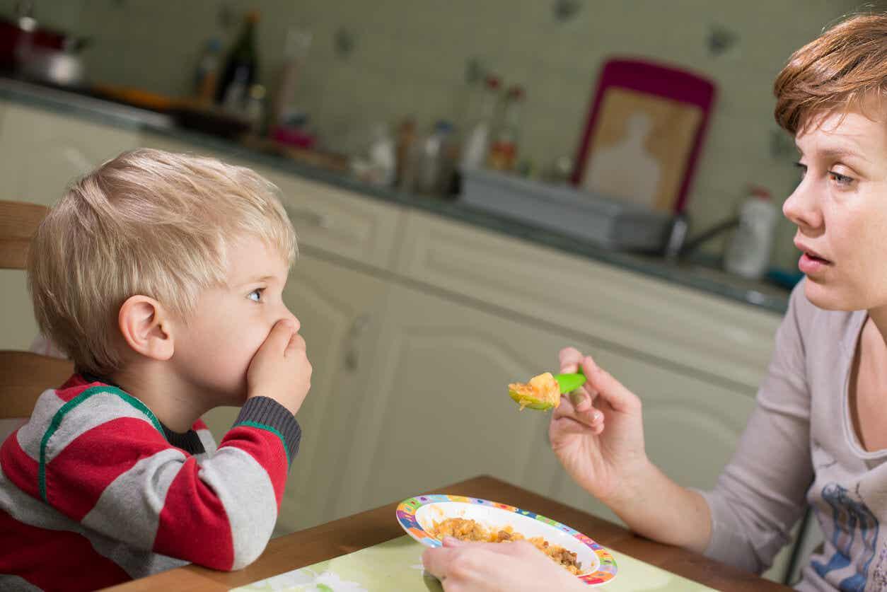 Een jong kind bedekt zijn mond terwijl zijn moeder hem probeert te voeden.