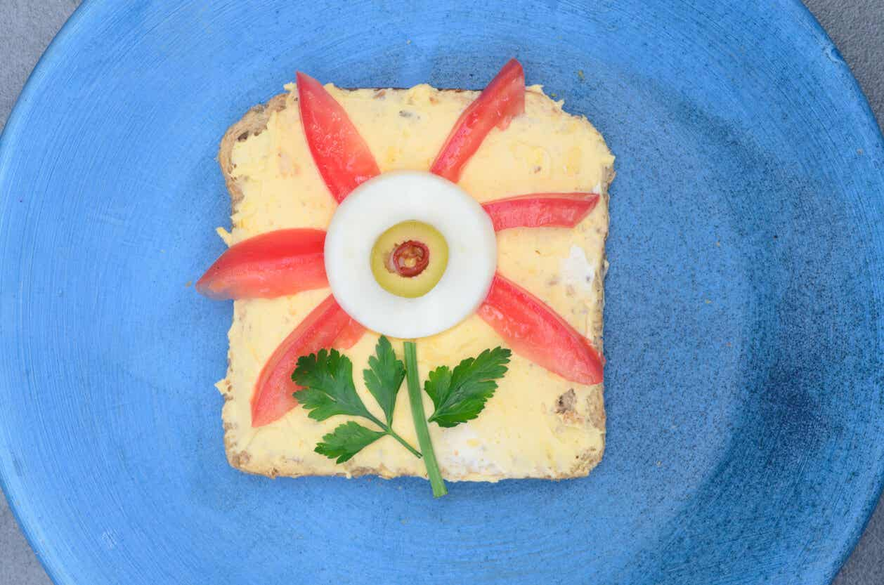 A egg sandwich with tomato wedges and an egg slice forming the shape of a flower.
