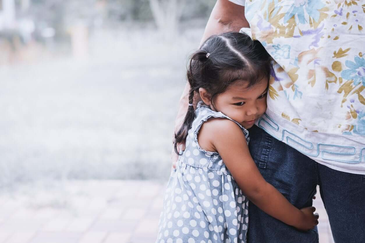 A young girl clinging to her father's leg.