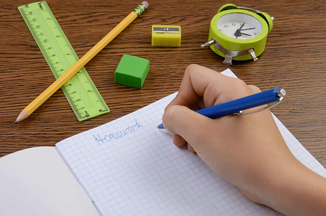 A child writing in their school notebook with an alarm clock nearby.