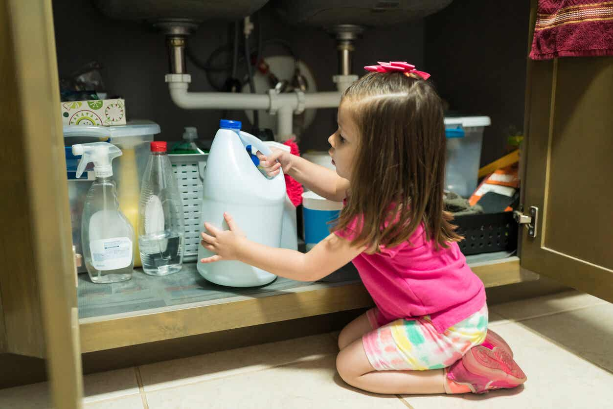 A toddler pulling a bottle of bleach from under the sink.