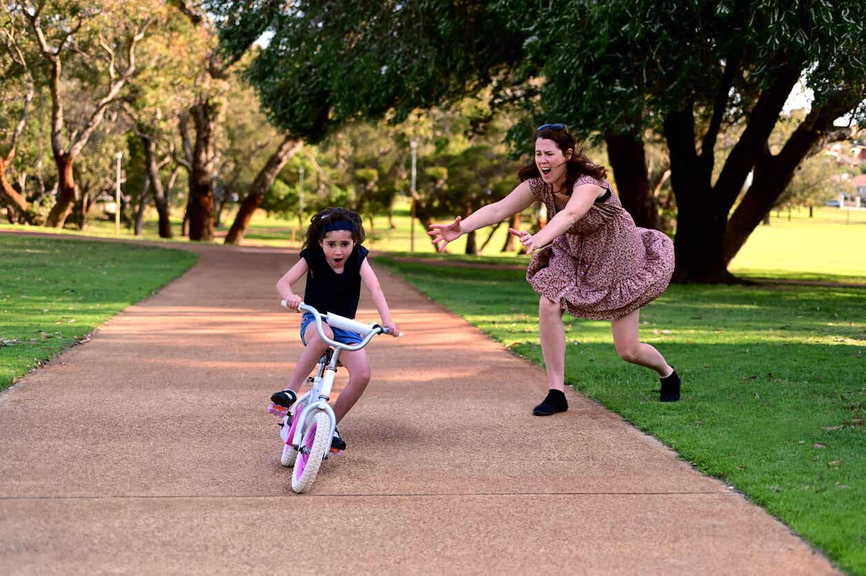 En mamma springer för att hjälpa sin dotter som tappar balansen på sin cykel.