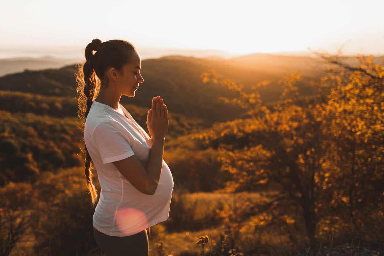 Een zwangere vrouw die mediteert in de natuur.
