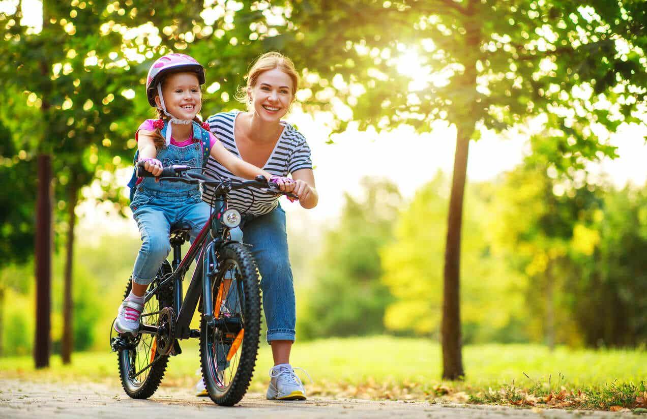 En mamma som lär sin dotter att cykla.