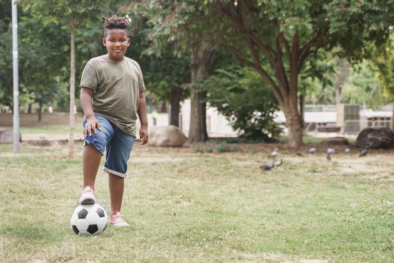 Dziecko z nadwagą grające w piłkę nożną.