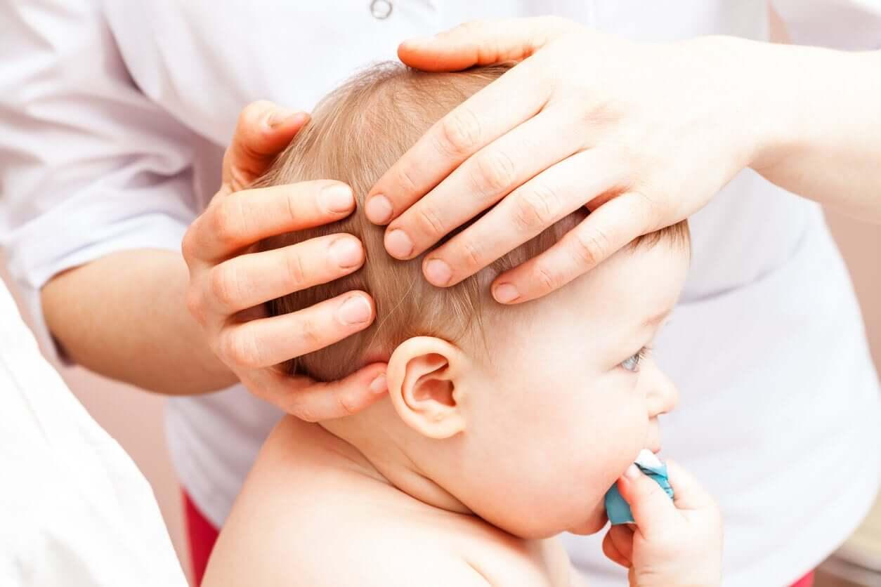 En läkare som undersöker ett barns huvud.