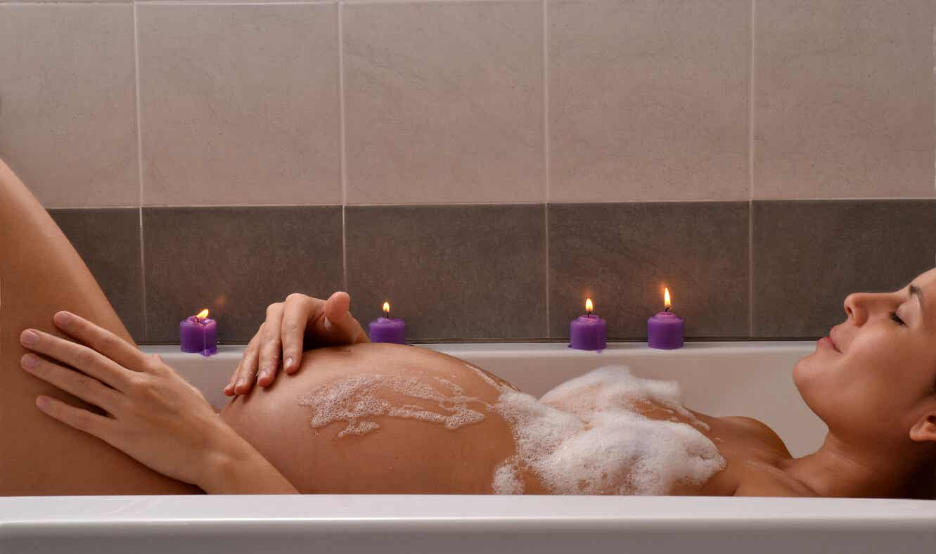 A pregnant woman in a bathtub with candles.