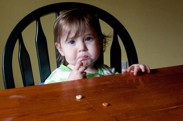 A toddler sitting at the dinner table looking stressed.