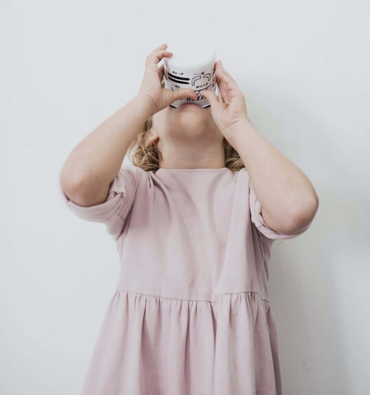 A young girl drinking yogurt.