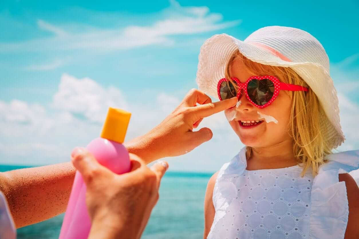 En mamma som applicerar solskyddsmedel på sin dotters ansikte på stranden.