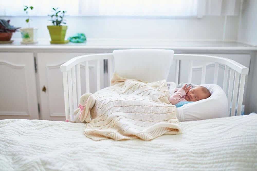 Baby sleeping in co-sleeping bed.
