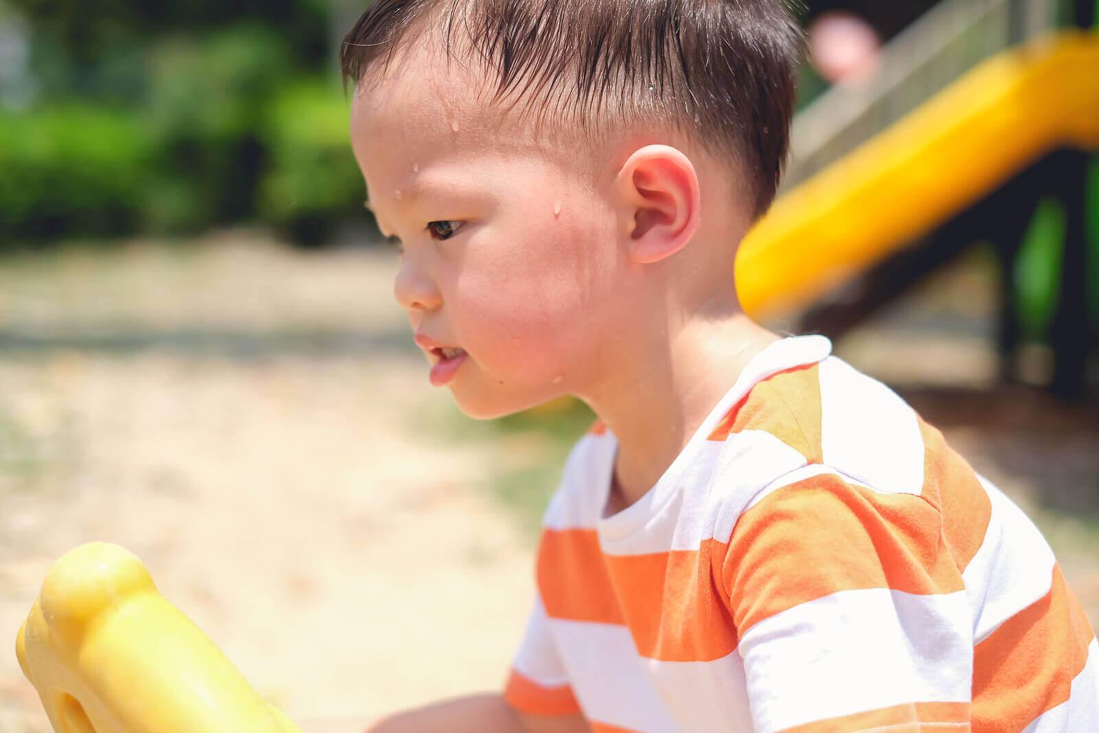 Pojke svettas mycket för att han leker i solen.