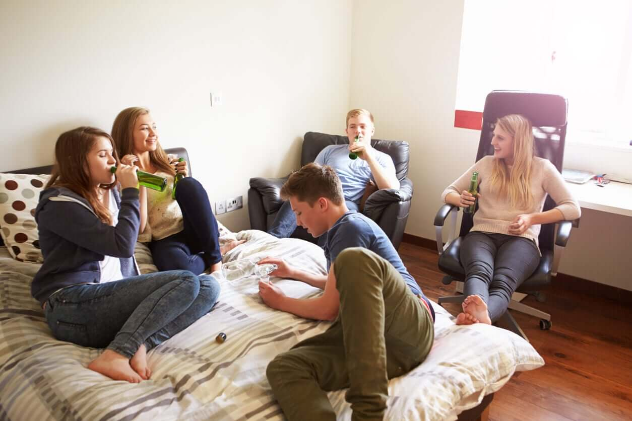 Teenagers hanging out in a bedroom drinking.