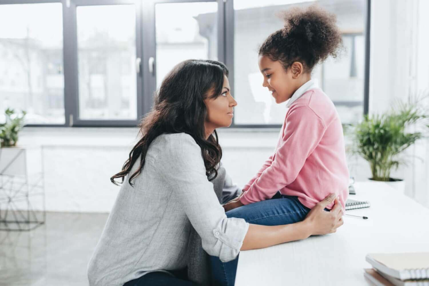 A mother looking into her daughter's eyes as they talk.