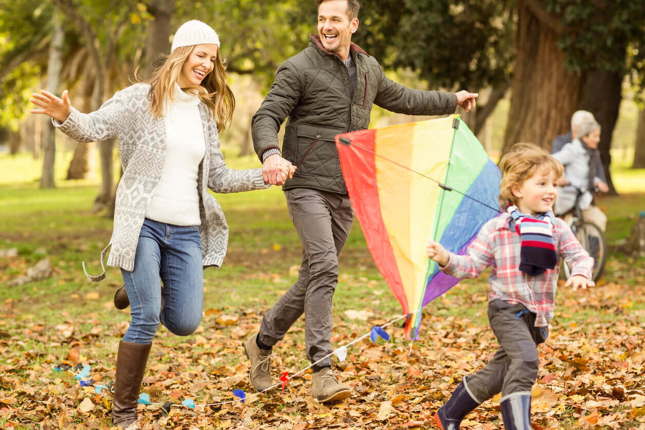 A family running outdoors with a kite.