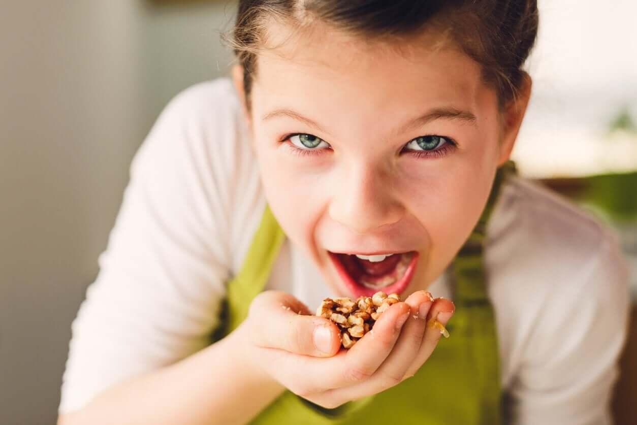 Et barn som putter granola i munnen hennes.