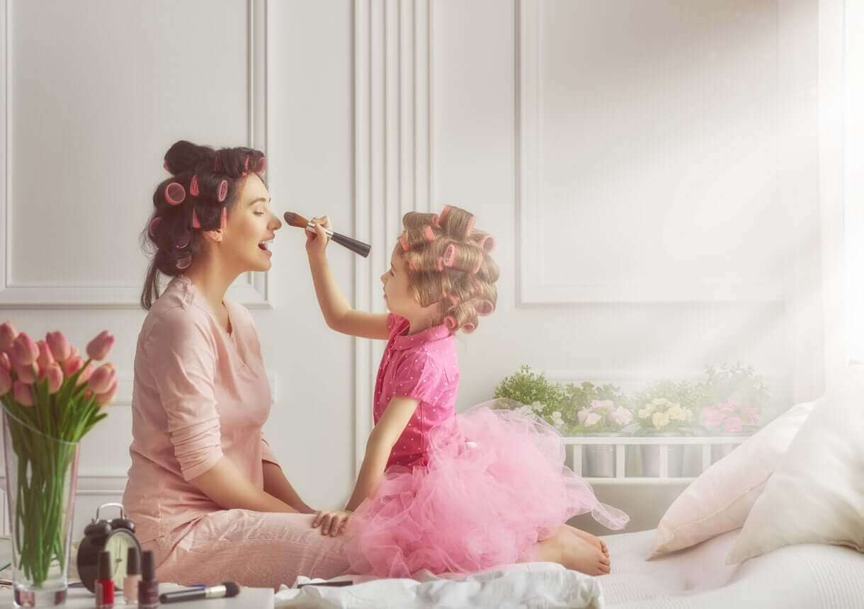 En datter som legger sminke på morens ansikt mens de begge bruker curlers i håret.