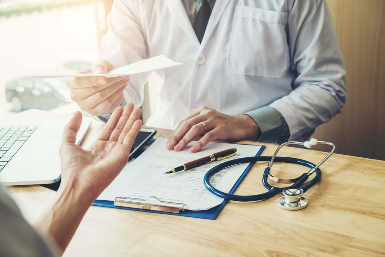 En lege som gir resept til en pasient.