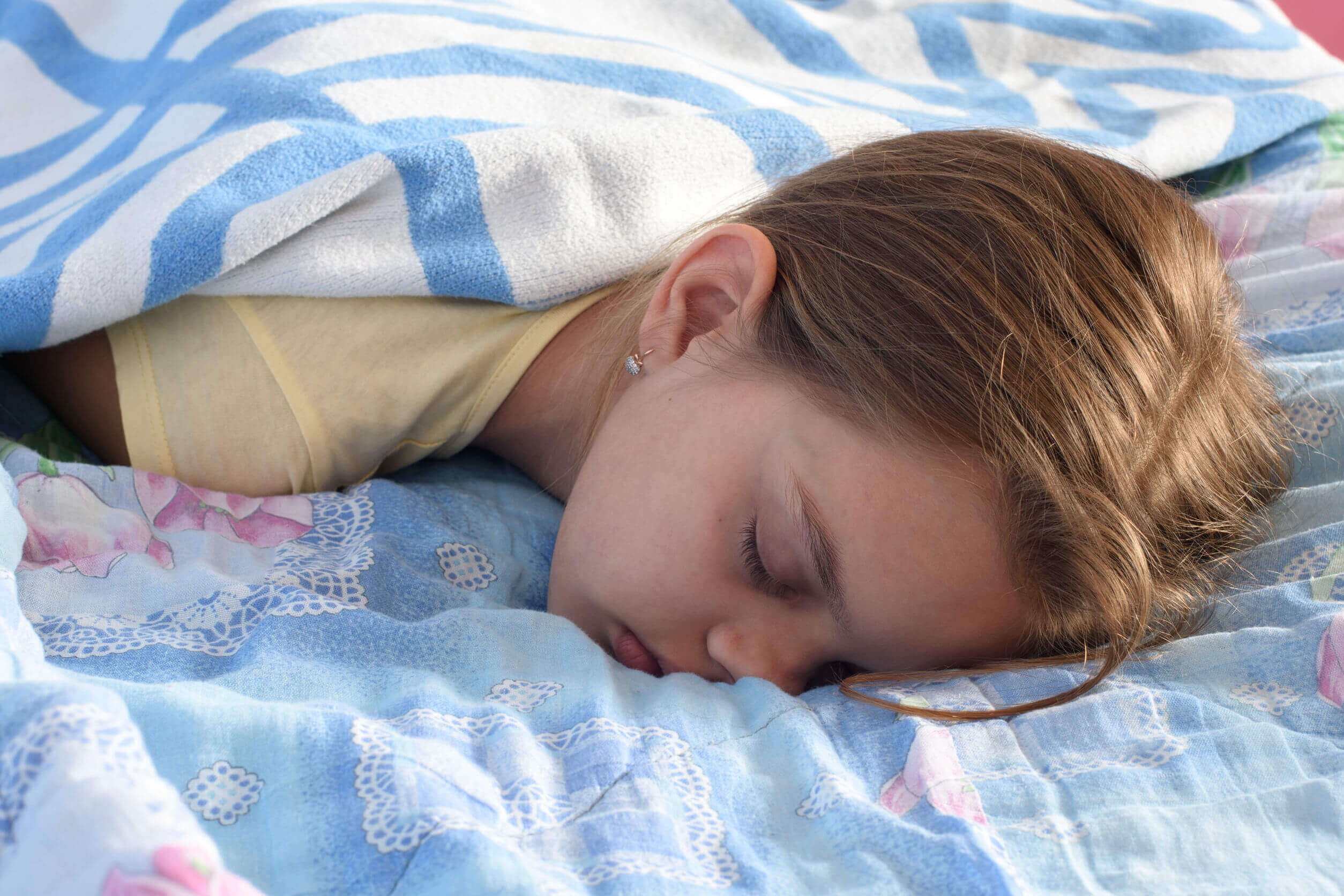 A teenage girl sleeping facedown on her bed.