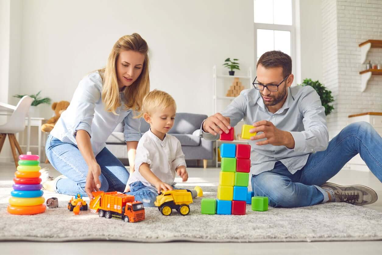 Parents playing with toys with their baby on the floor.