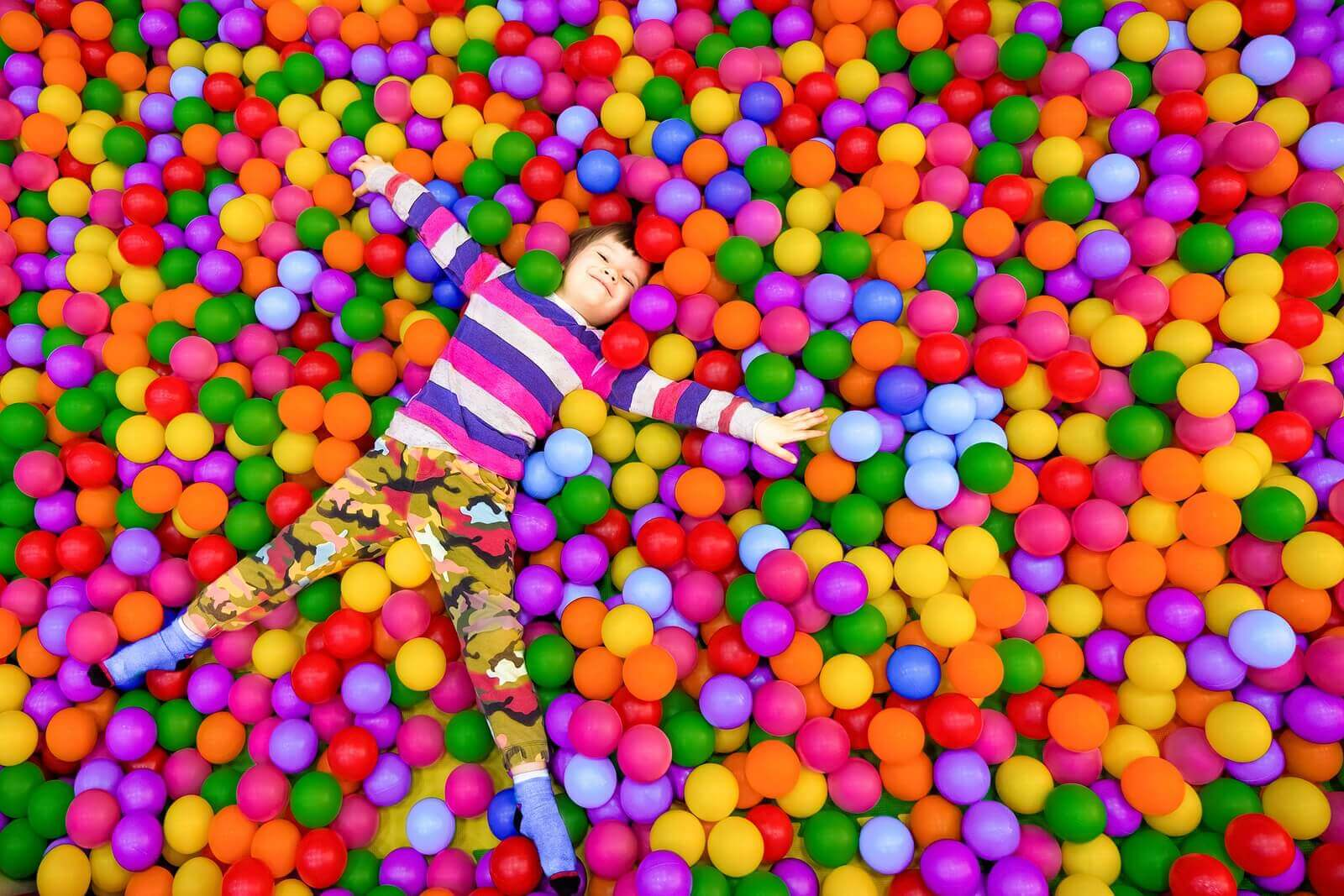 Een kind ligt in een ballenbak