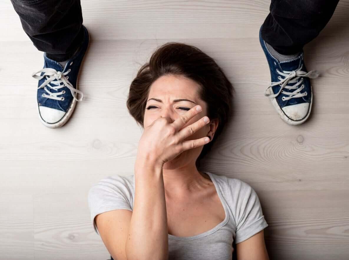 En kvinna stoppar näsan eftersom hennes tonårs son fötter luktar.