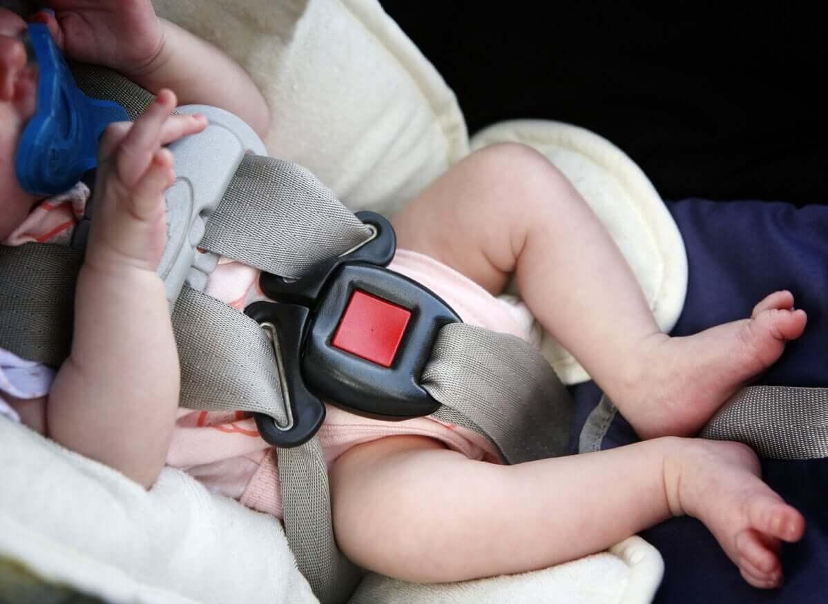 En nyfödd flicka i en bilbarnstol.