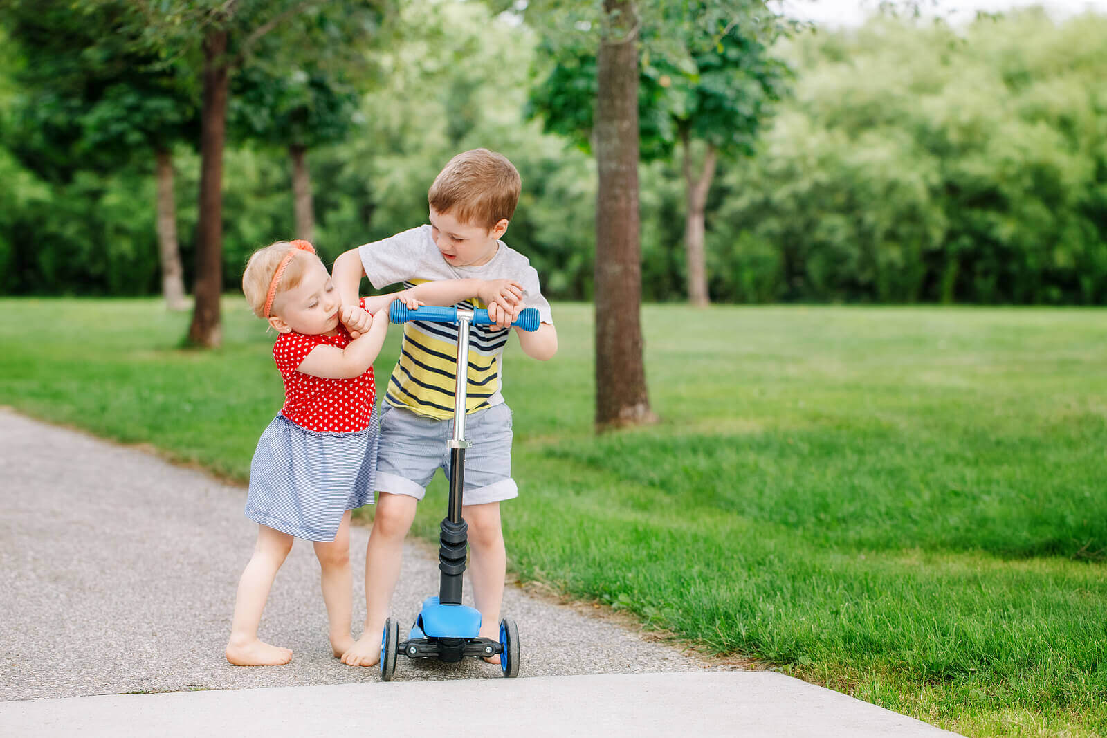 A boy and his little sister fighting over a scooter.