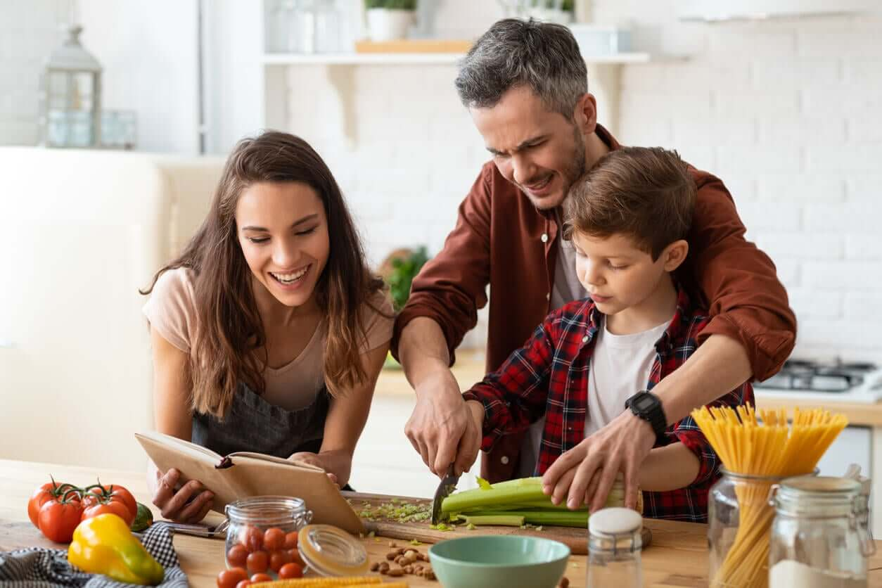 En far og mor som tilbereder mat sammen med sønnen.