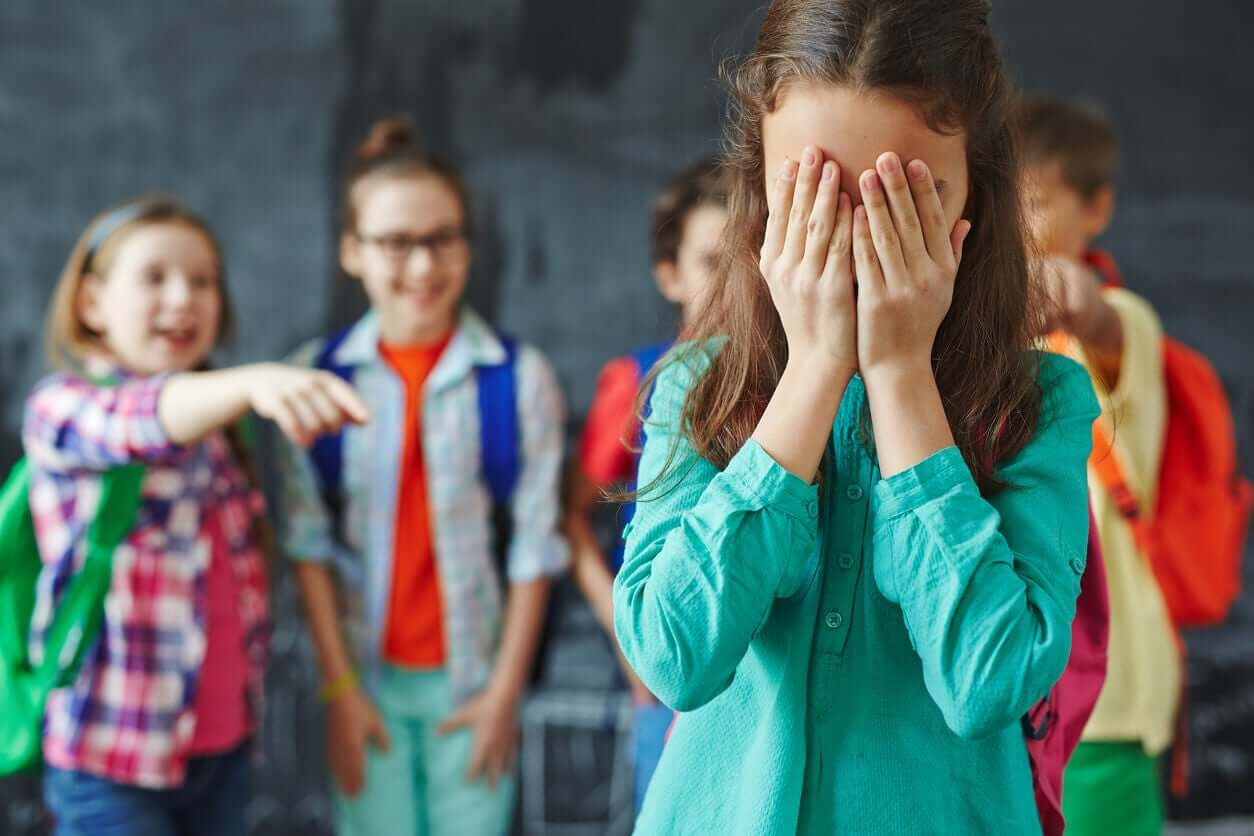 Students laughing and pointing at their classmate who's covering her face with her hands.