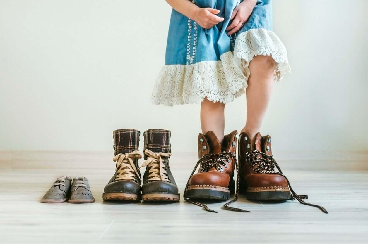 En liten jente som prøver på farens sko.