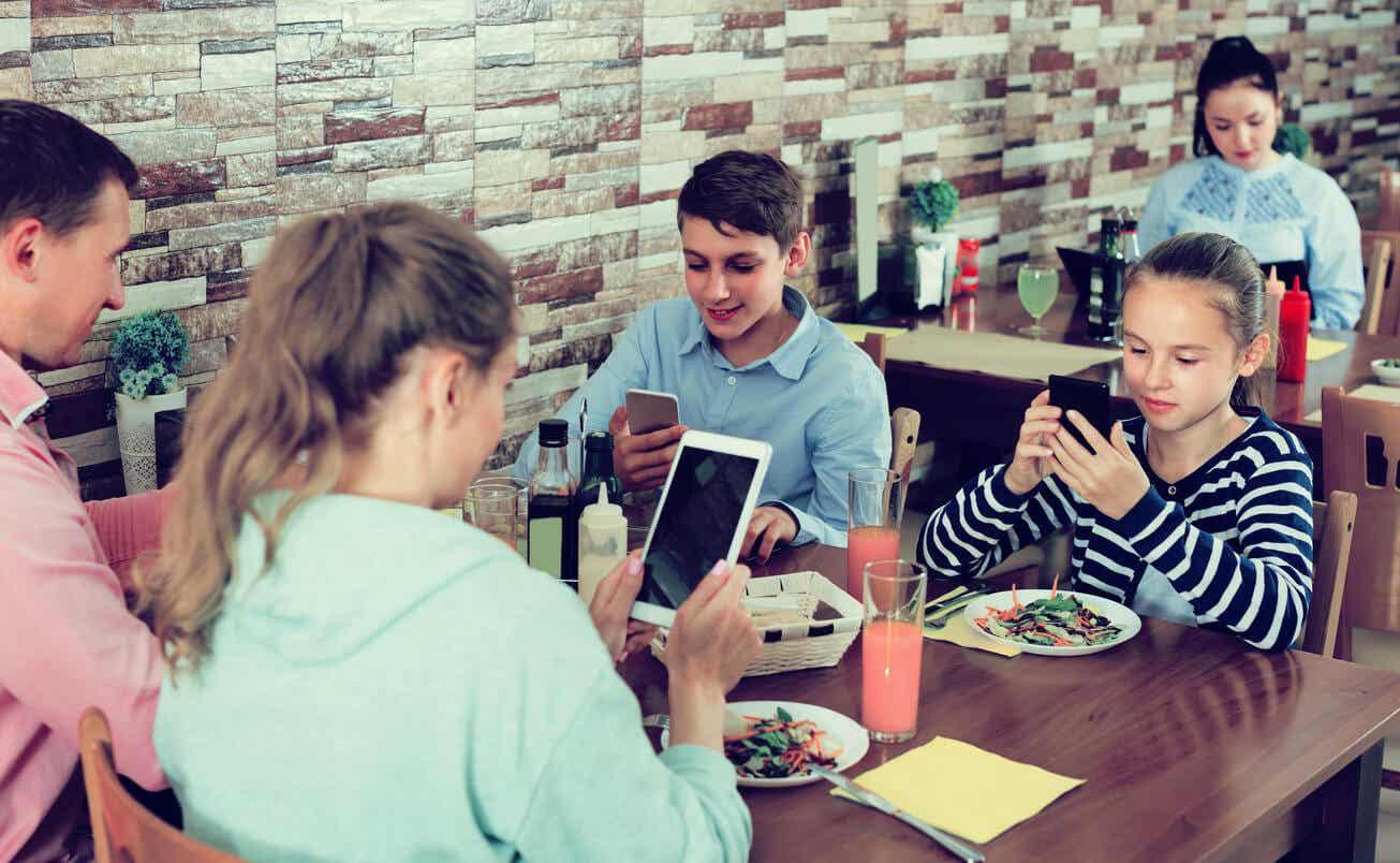 Rodzina z telefonami w restauracji