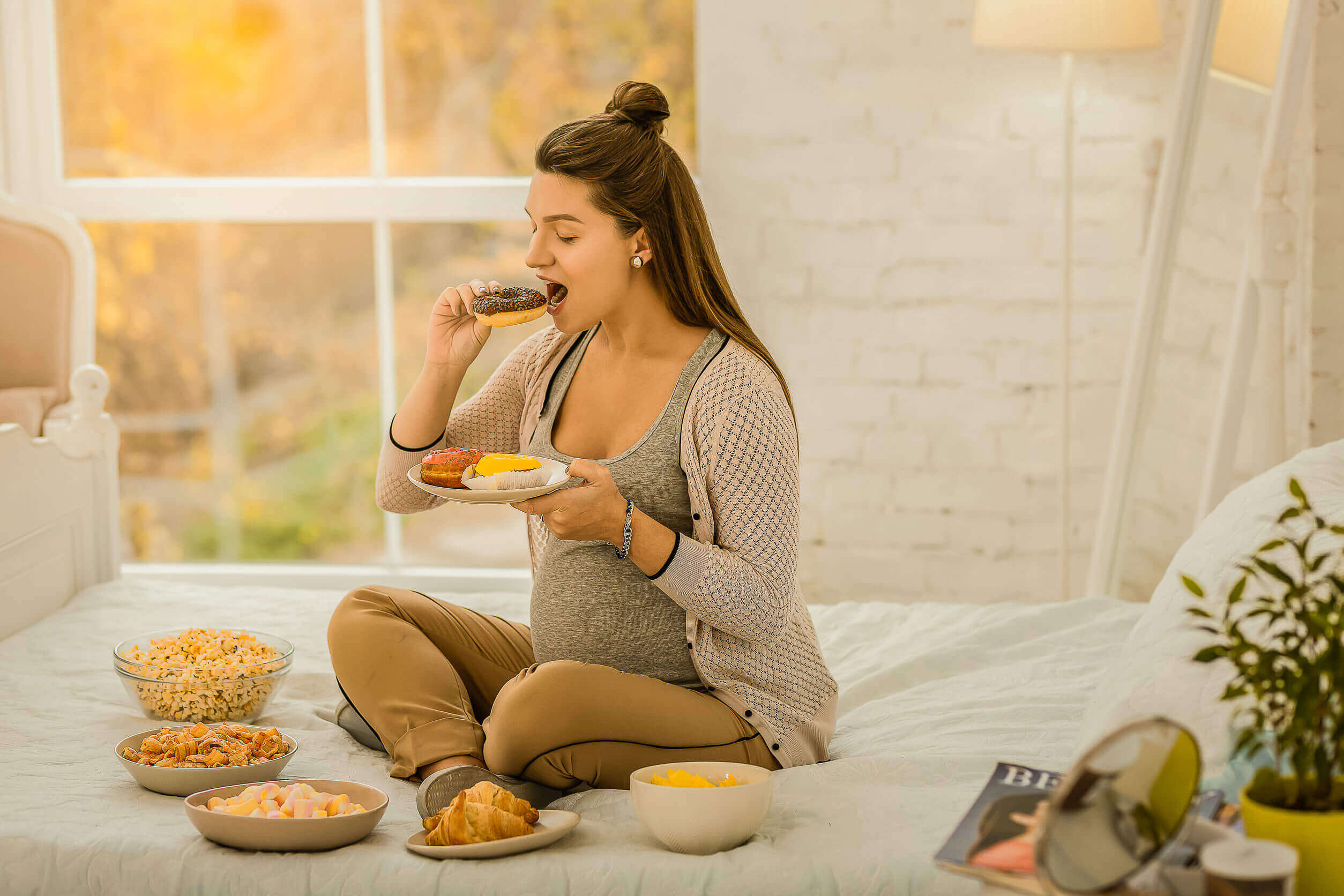 En gravid kvinne som snakker i sengen og spiser søtsaker.