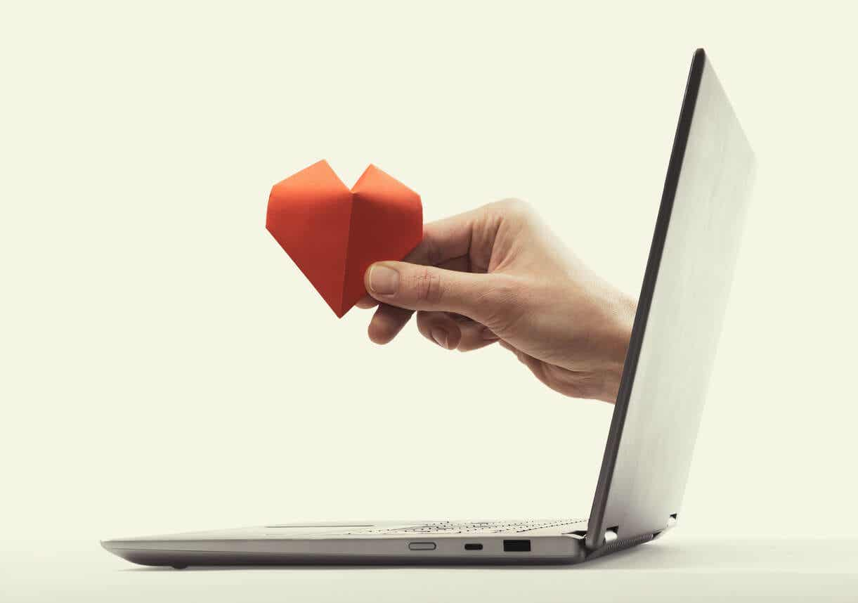 A hand reaching out from the screen of a laptop, holding a paper heart.