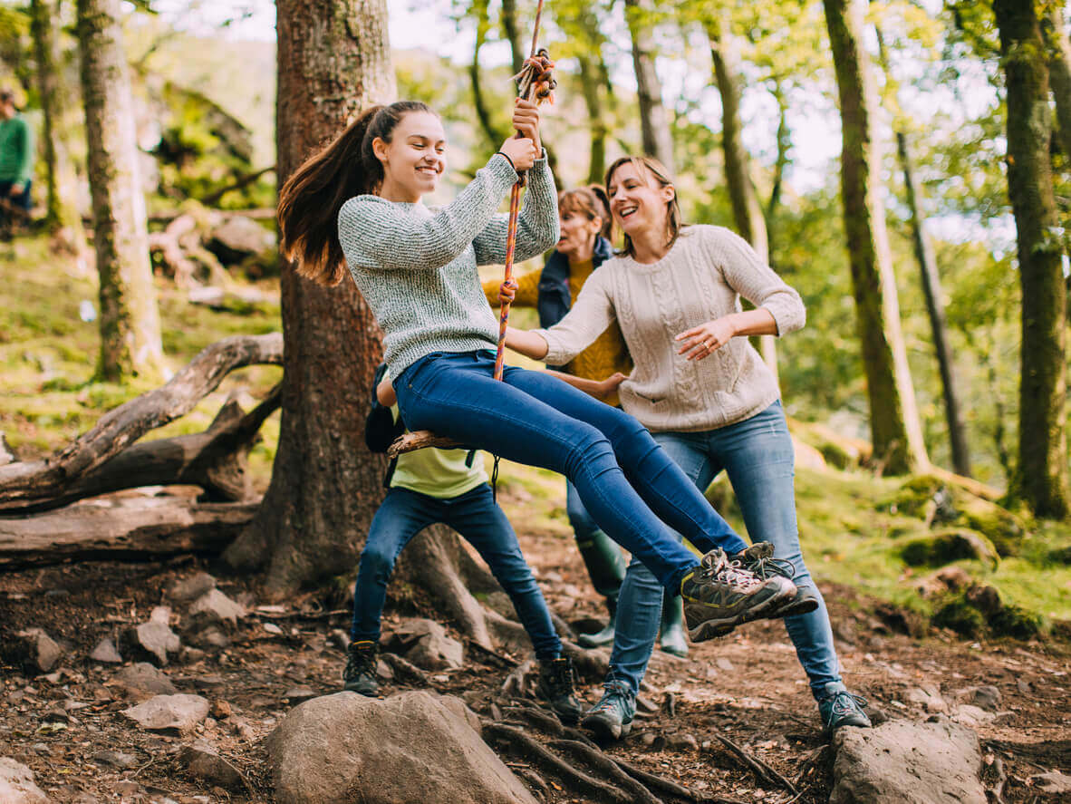 Teenagers playing on a rope swing in the woods.