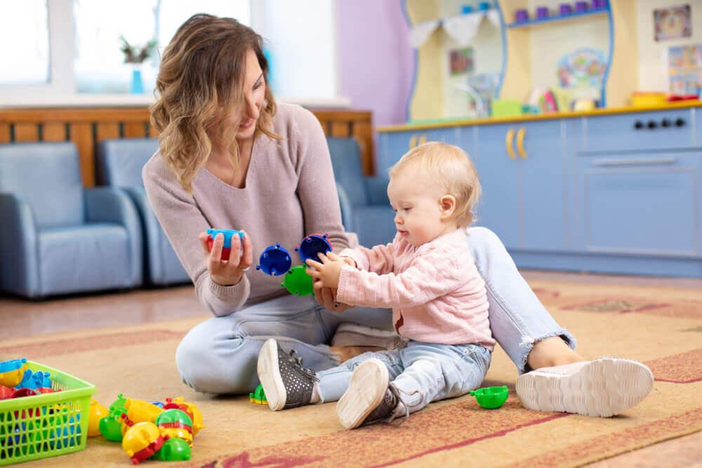 En mor sitter på gulvet og leker med jenta hennes.