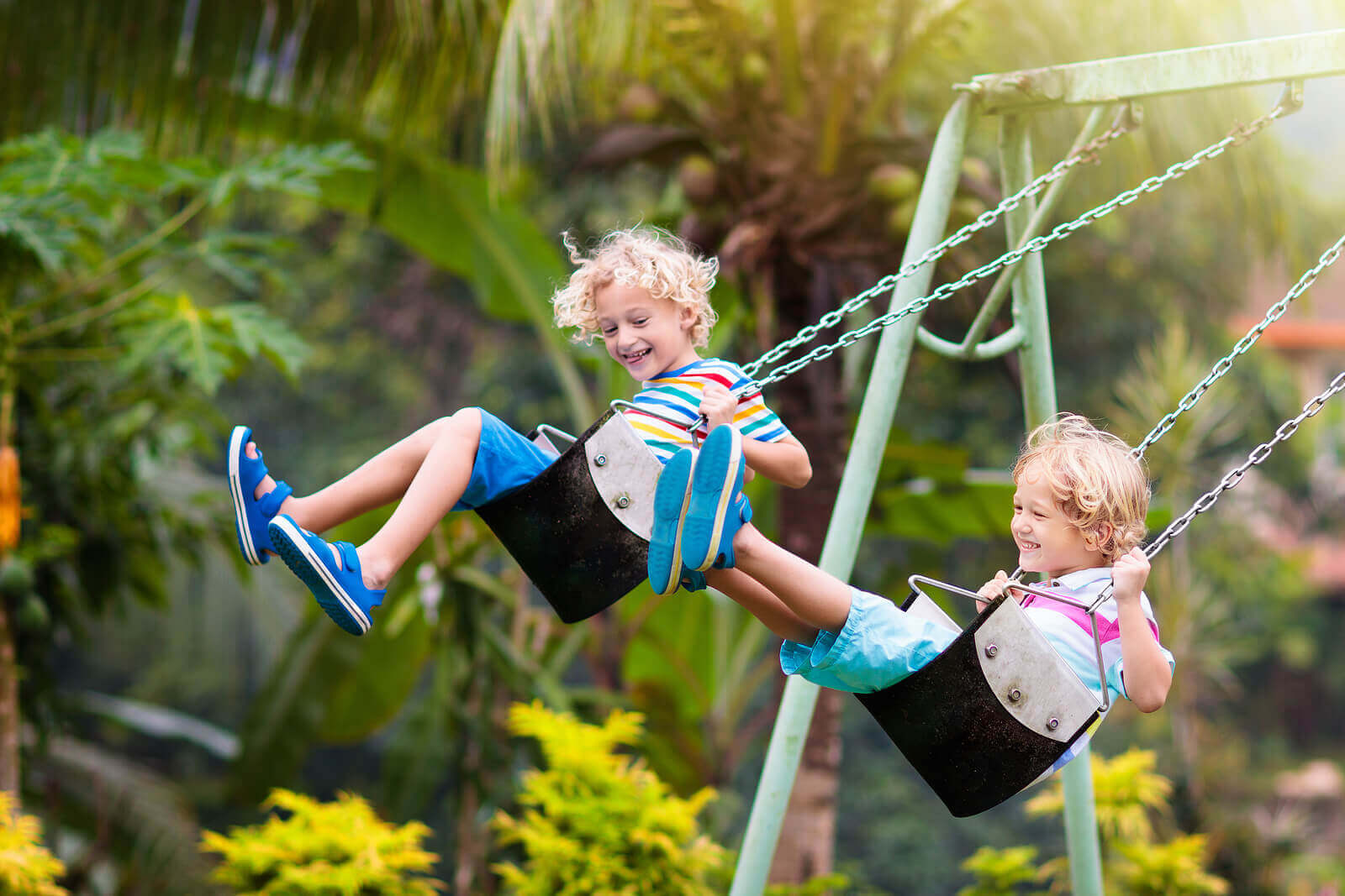 Two brothers swinging on a swingset.