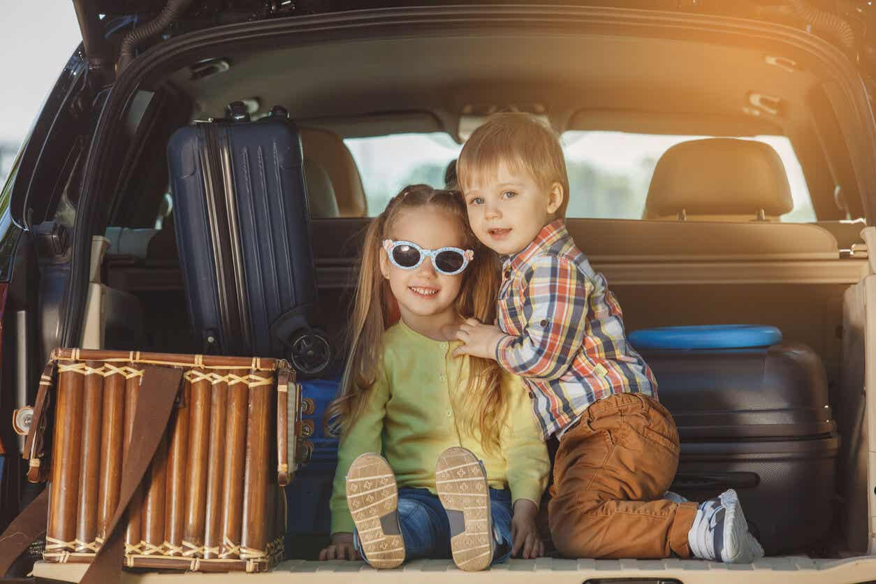 Two chidren sitting in the back of a SUV getting ready to go on a trip.